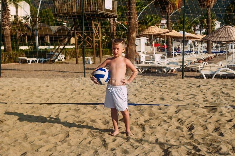 Garbnikująca poważna siedmioletnia chłopiec w biel plaży skrótach z piłką na piasek siatkówki sądzie, wakacje zdjęcia royalty free