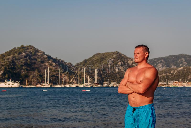 Garbnikujący Kaukaski mężczyzna w błękitnym kąpaniu zwiera stojaki na plaży w Turcja obraz stock
