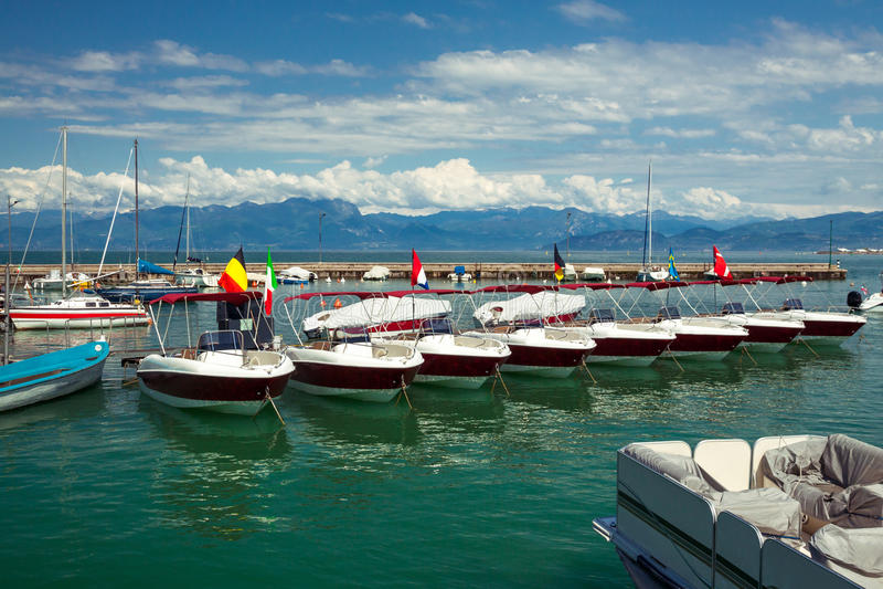 Garda Lake boats. Recreational small motorboats docked in bay on Garda Lake, Peschiera del Garda, Italy. Boats rental for tourists stock photos