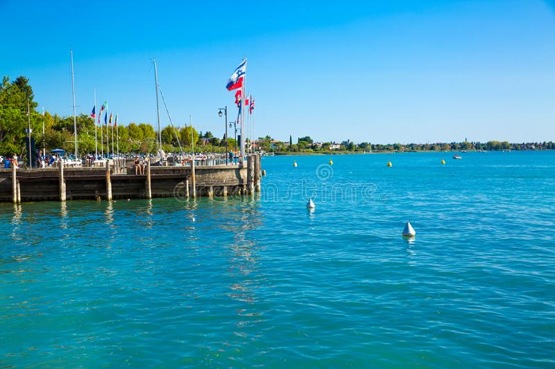 Garda lake, Sirmione, Italy. Port in lake Garda. Different flags. In the port royalty free stock photography