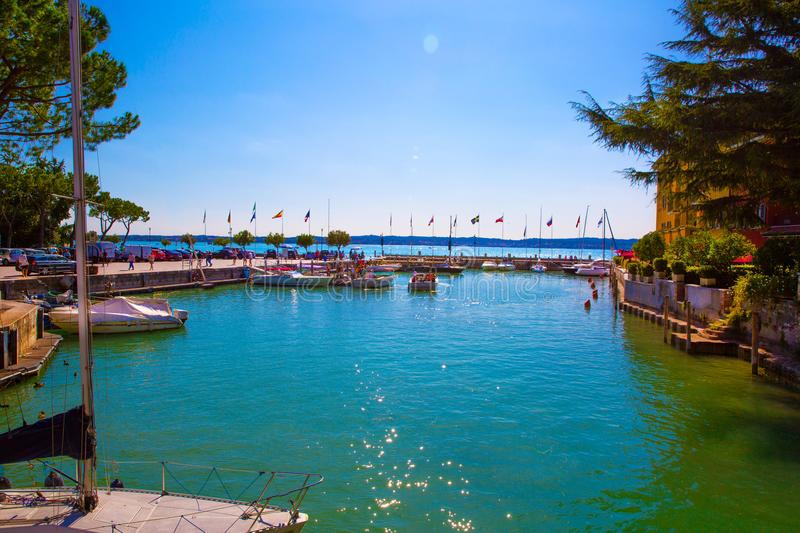 Garda lake, Sirmione, Italy. Port in lake Garda. Different flags. In the port stock image