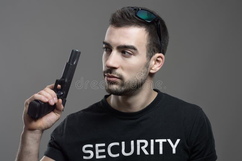 Garde de sécurité alerté prudent tenant l'arme à feu regardant en arrière au-dessus de l'épaule photographie stock