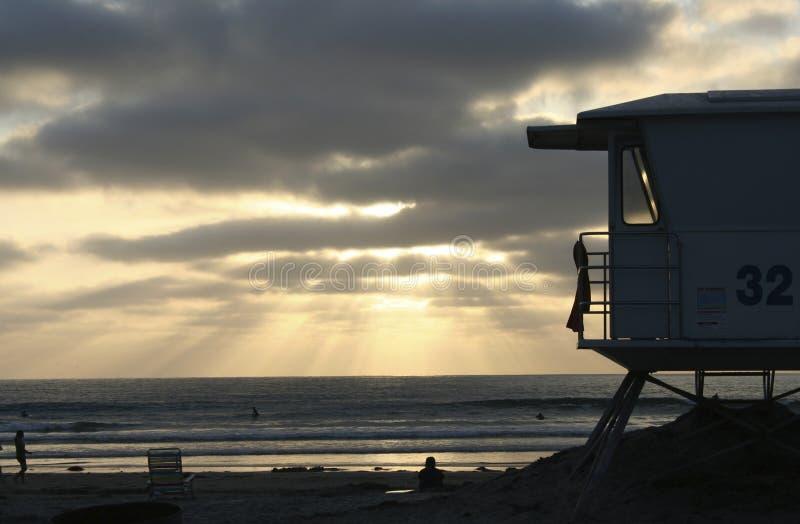 Garde de vie Tower en silhouette à la plage au coucher du soleil photos stock