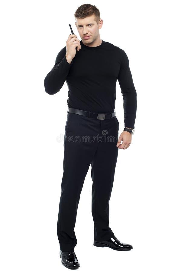Garde du corps communiquant par l'intermédiaire du talkie-walkie photo libre de droits