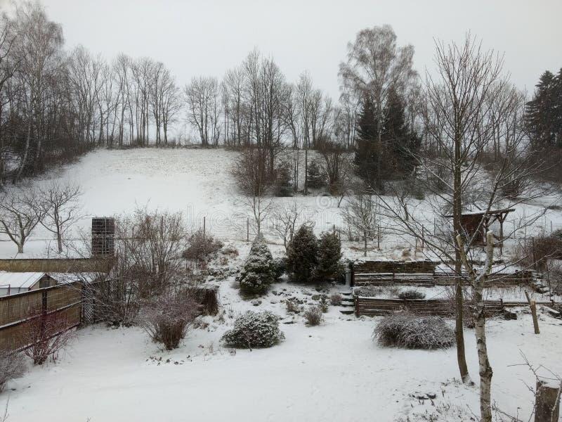 Garde n om vinterdagen med snö arkivbilder