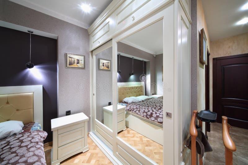 Garde-robe blanche intégrée avec les portes reflétées dans la chambre à coucher image libre de droits