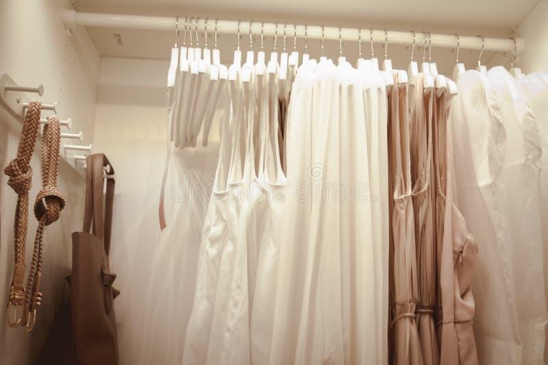 Garde-robe en bois moderne avec des v?tements accrochant sur le rail Stockage et entretien des vêtements à la maison images libres de droits