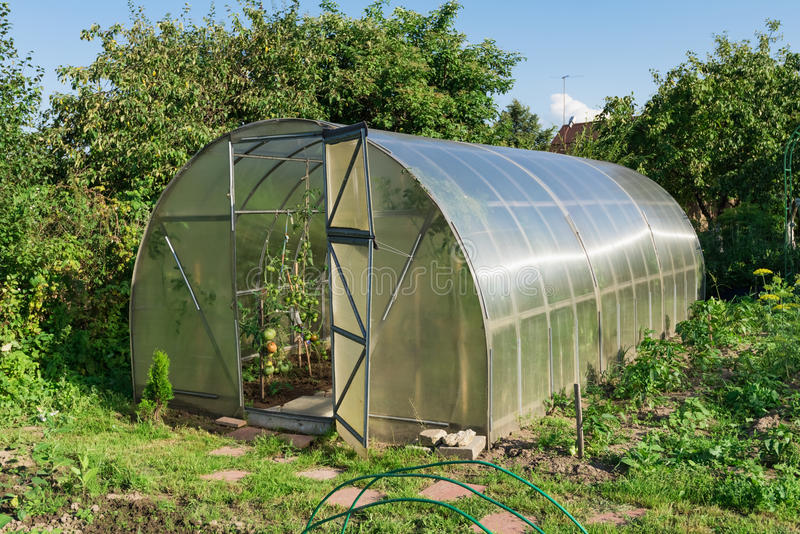 In the garden arched greenhouse stock photography