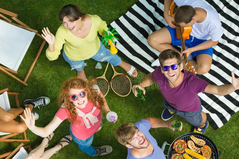 Garden barbecue and grill party. High angle photo of group of young friends waving at camera while enjoying garden barbecue and grill party, having fun royalty free stock image