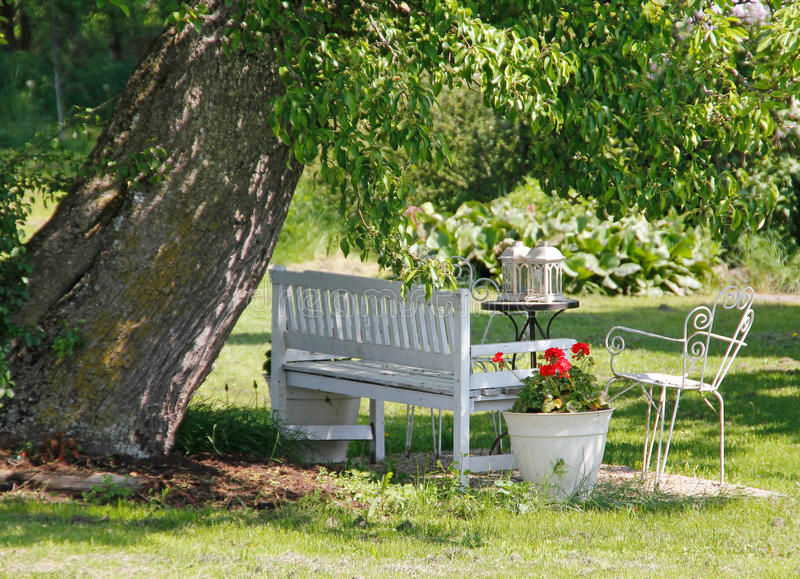 Garden-bench. A lovely garden scene with a bench, an iron chair and an iron table with two lamps on it, all in white, in the shadow of a big tree royalty free stock photos