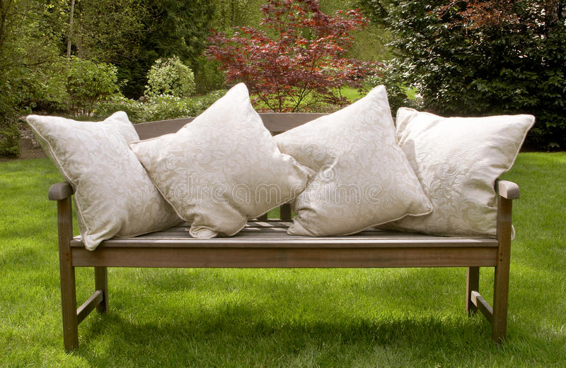 Garden bench cushions. Wood garden bench with large cream cushions royalty free stock images