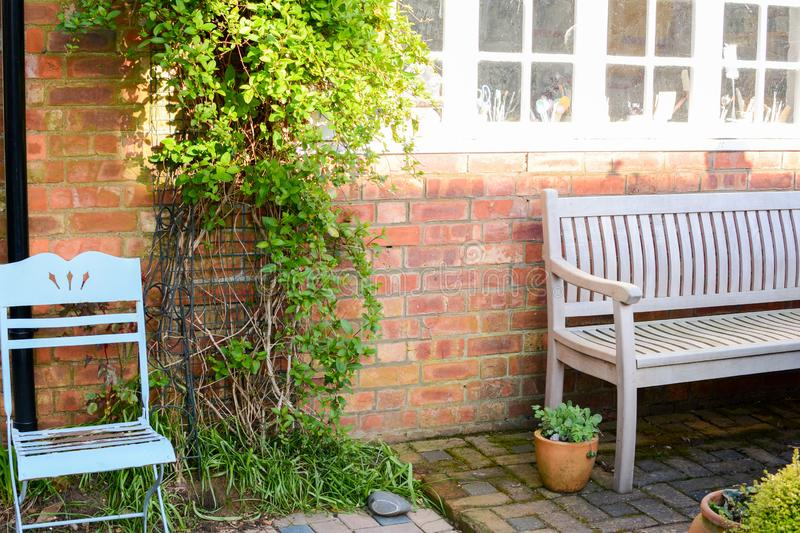 Garden patio. Garden bench and outdoor furniture on a patio royalty free stock images