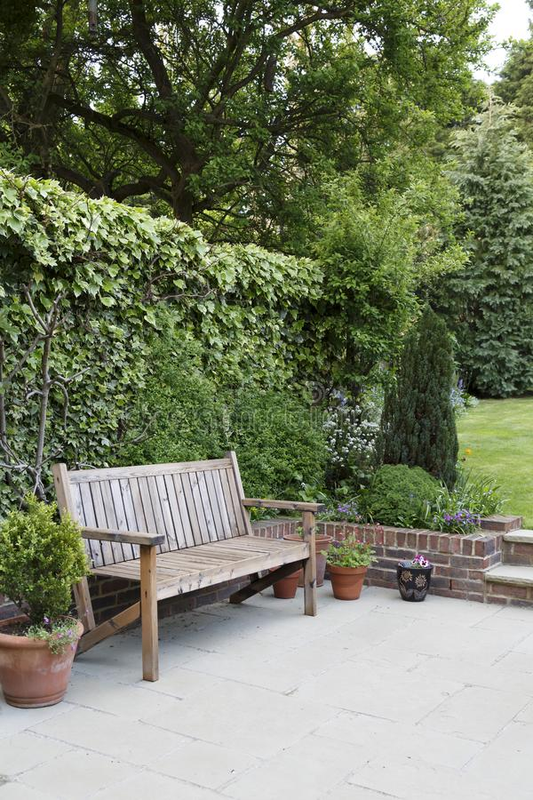 Garden with bench and patio. A typical English back garden in the UK, with flag stone patio and wooden bench patio furniture royalty free stock photo