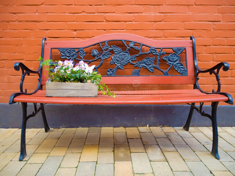 Garden benck with flowers. Vintage bench of wood and cast iron with flowers royalty free stock image