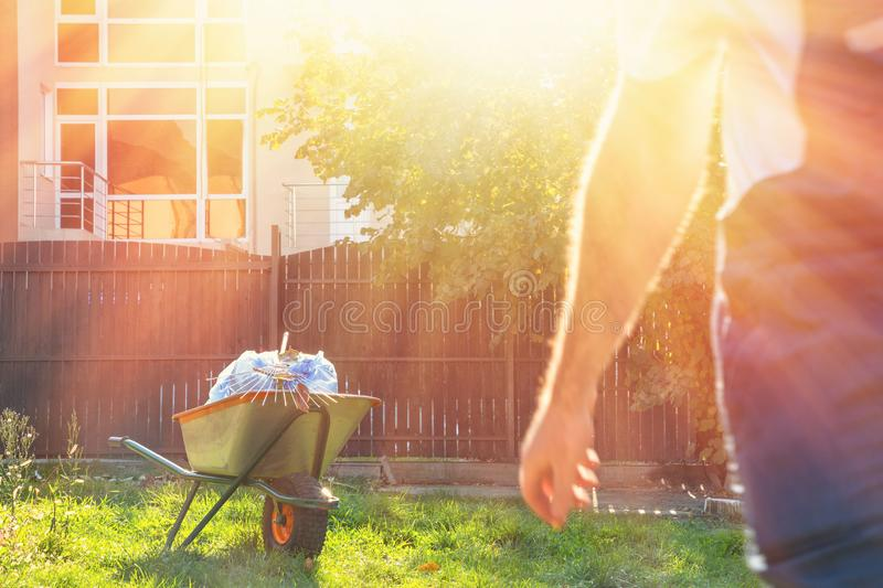 garden cart with garbage bags and rake on the background of a walking man in a gardener`s uniform.in the bright sun royalty free stock photos