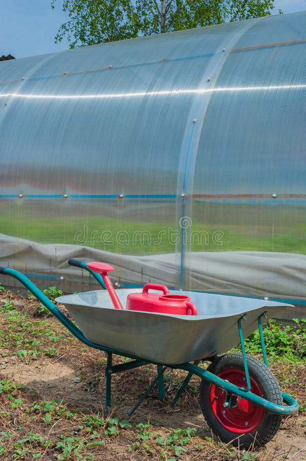 Garden cart and watering can royalty free stock photography