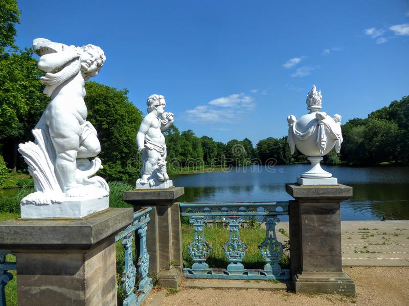 Garden of the castle of Charlottenburg in Berlin with a lake, trees and three white statues in front of, Germany. royalty free stock images