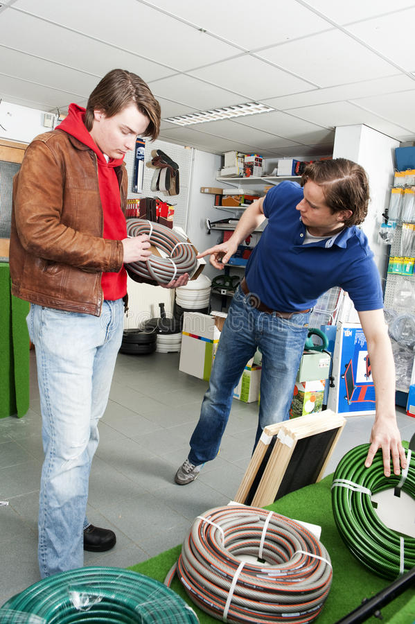 Garden center. Salesman advising a customer in the garden department of a hardware store royalty free stock images