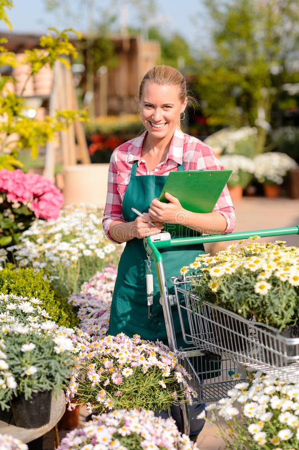 Garden center woman put potted flowers cart royalty free stock photo