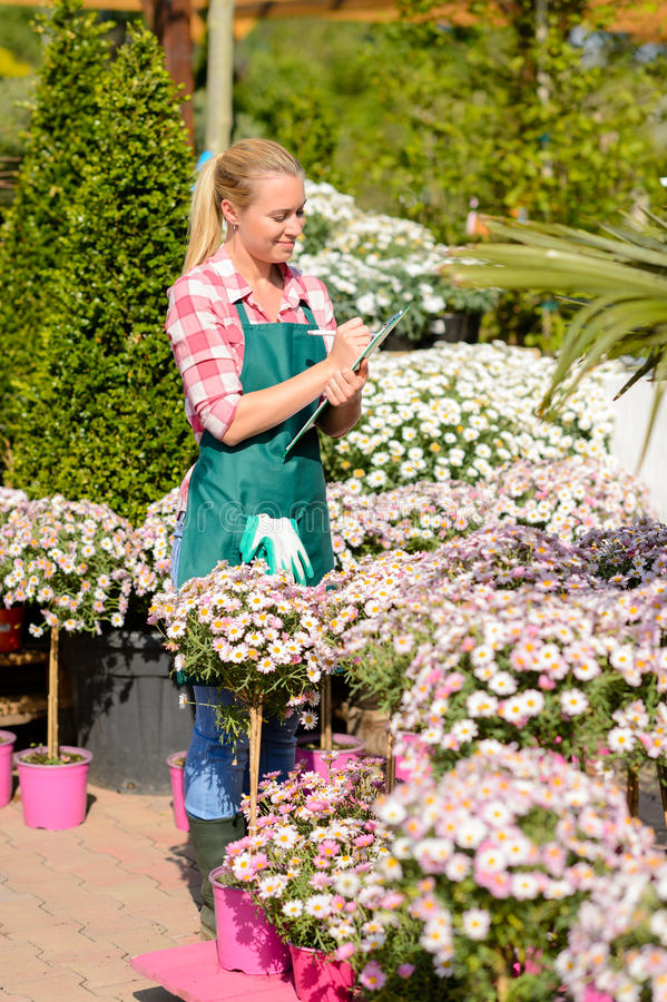 Garden center woman write notes potted flowers royalty free stock photos
