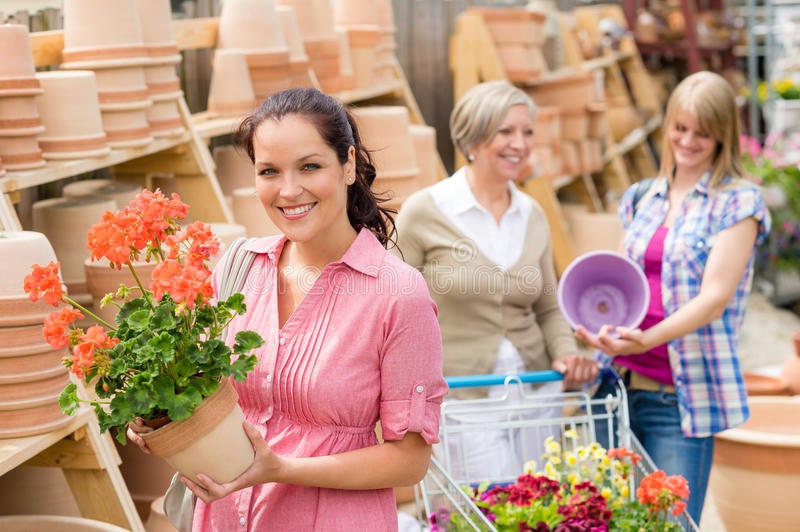 Garden centre woman hold red potted geranium royalty free stock photos