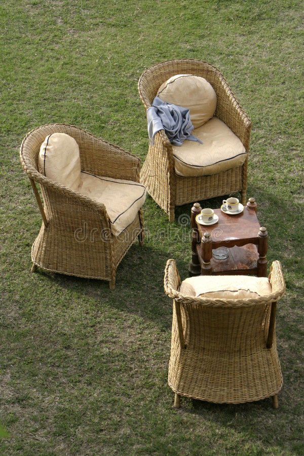 Garden chairs. Cane chairs in the garden royalty free stock images
