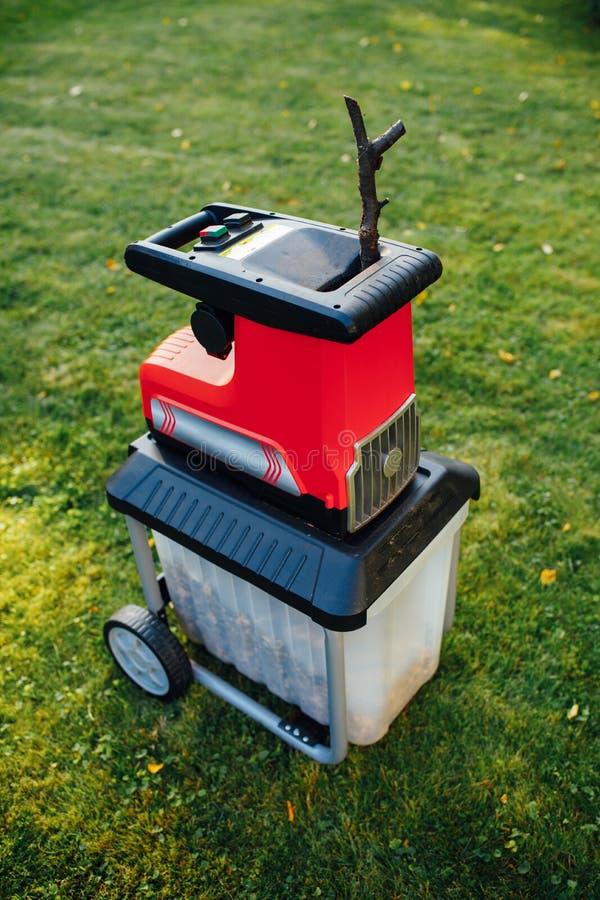Garden chipper, electric shredder mulcher. Green grass background stock photography