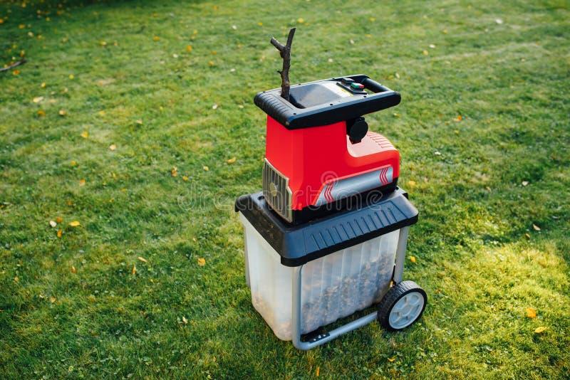 Garden chipper, electric shredder mulcher. Green grass background royalty free stock image