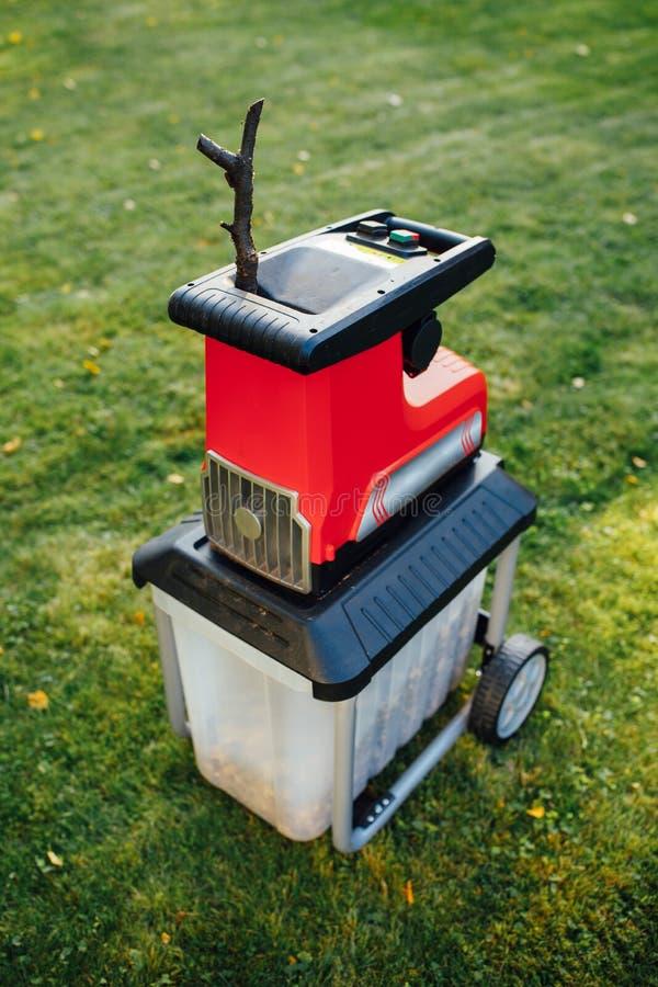 Garden chipper, electric shredder mulcher. Green grass background stock images