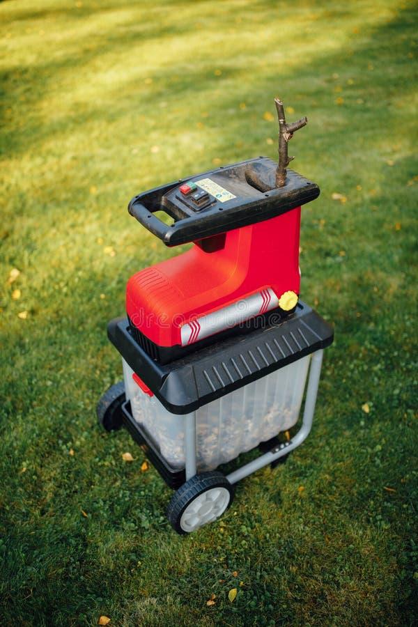 Garden chipper, electric shredder mulcher. Green grass background stock image