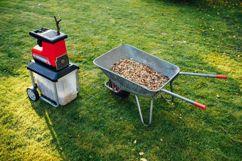 Garden chipper, electric shredder mulcher with wheelbarrow full of wooden mulch. Green grass background stock photo