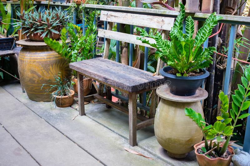 Garden Corner in Thai House. Old wood bench and plants at garden corner on the outdoor balcony in Thai house royalty free stock photos