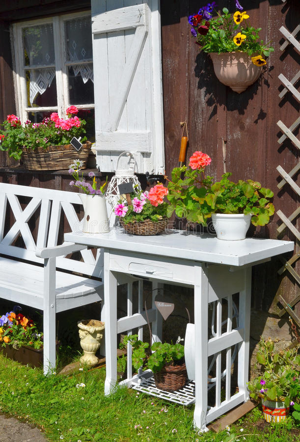 Garden Cottage in the summer. With white furniture and many flowers royalty free stock photo