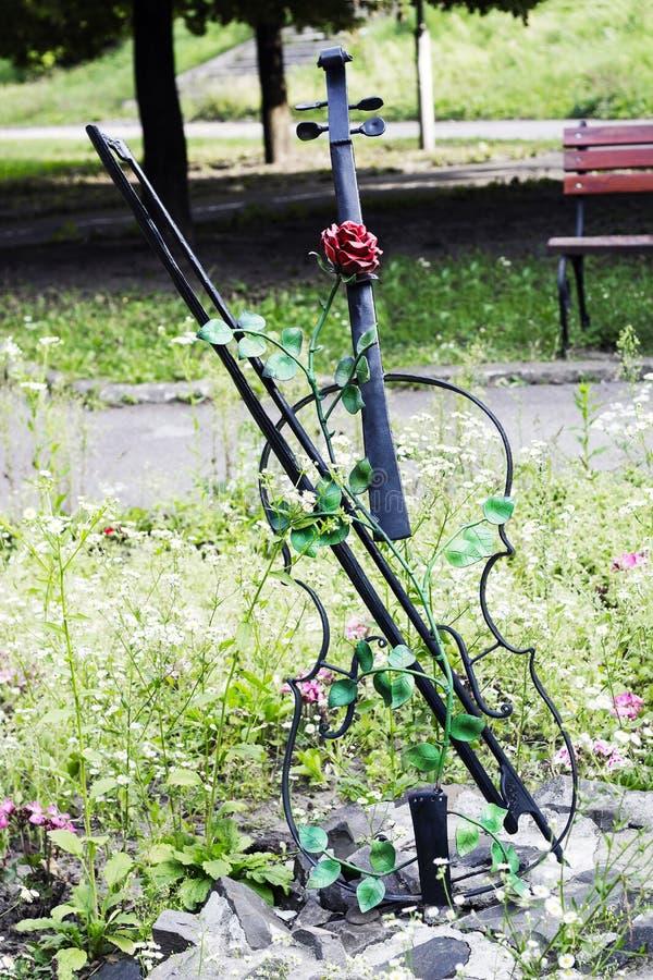 Garden decor metal violin with red rose stock photos