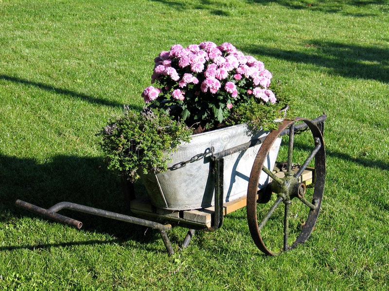 Garden decor in old wagon. A garden decorated with an old wagon turned into a planter stock image