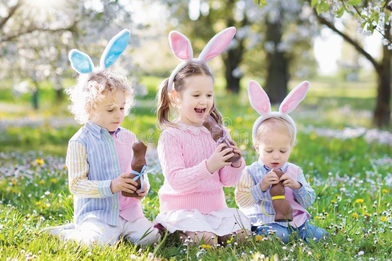 Garden Easter egg hunt. Kids eat bunny chocolate. royalty free stock photography