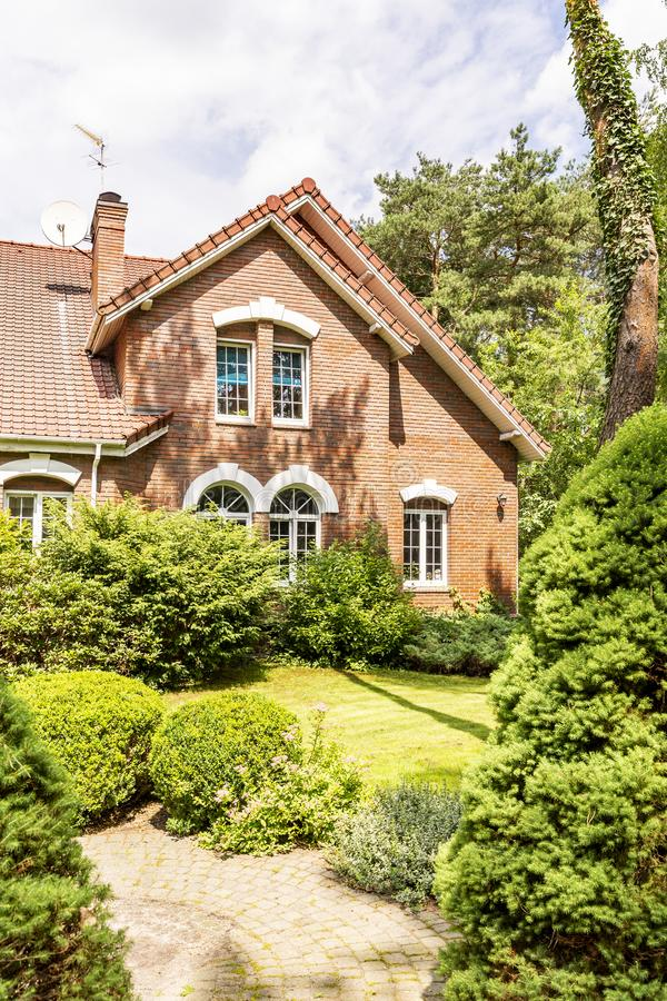 A garden with evergreens, trees, shrubs and grass in the backyard of a red brick luxurious English style house. stock photo