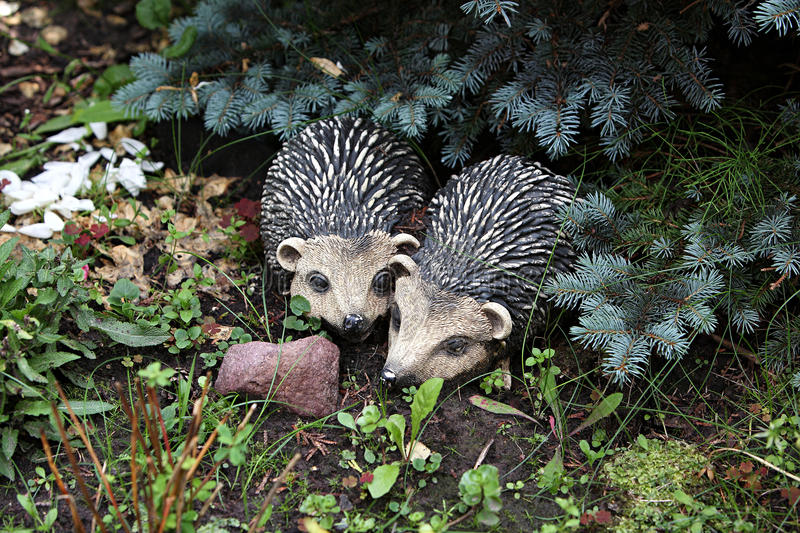 Garden figurines. Hedgehogs. Two figurines for a garden and giving in the form of hedgehogs in thickets of homestead plants stock photography