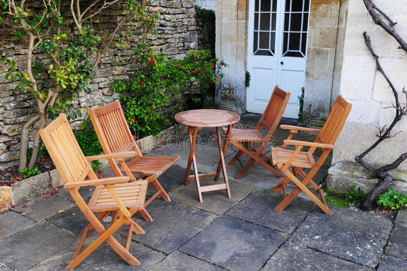 Garden Furniture on a Patio. Wooden Garden Furniture on a Stone Patio - Garden Background stock photos
