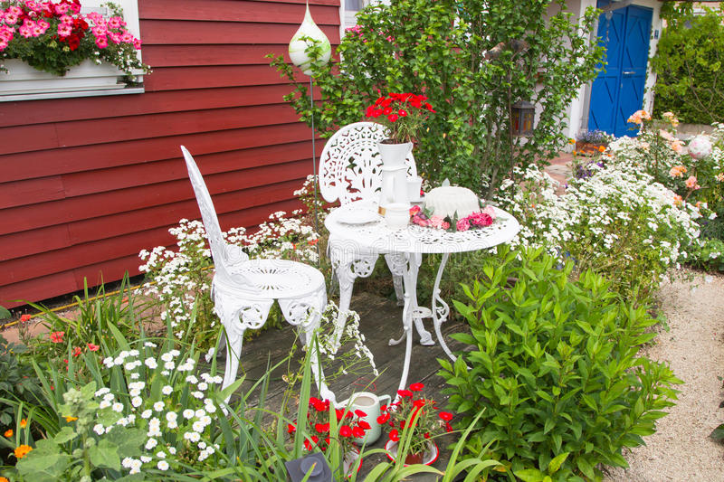 Garden furniture set with flowers in front of country house. stock photo