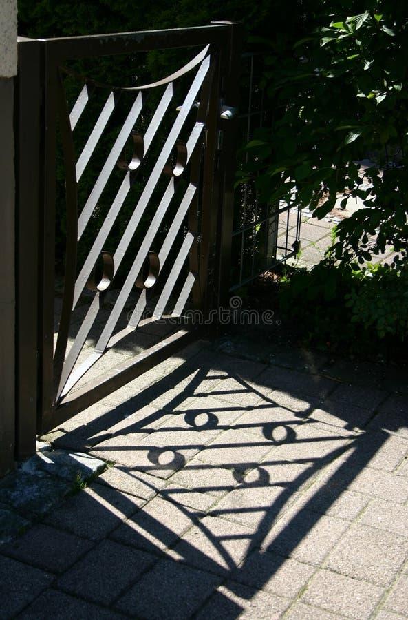 Garden gate. Ornate garden gate and shadow cast on the sidewalk royalty free stock photos