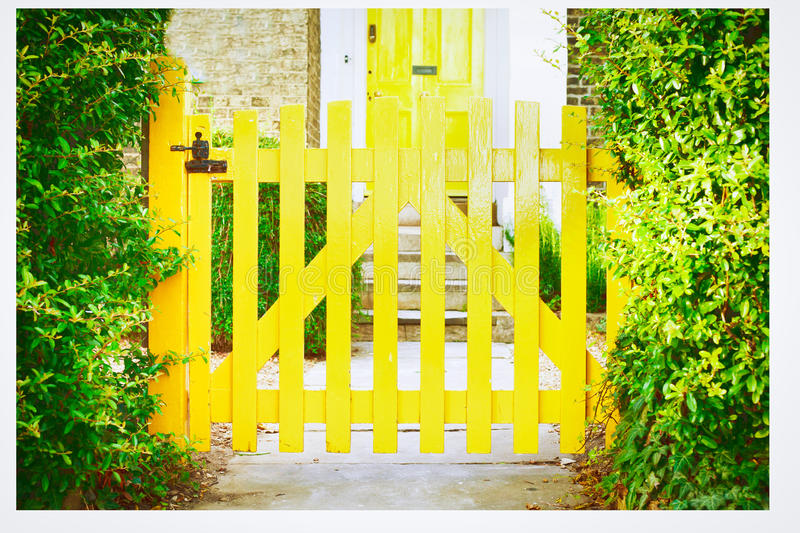 Garden gate. A nice yellow garden gate in front of an english house stock images