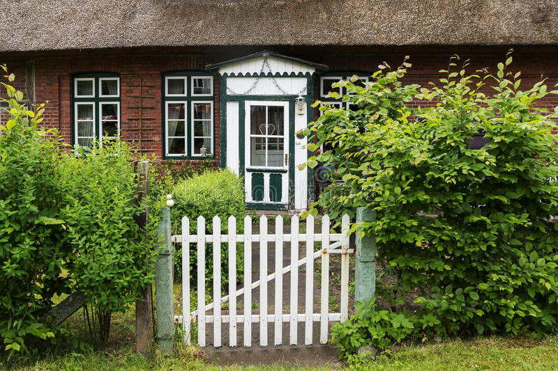 Garden gate and a beautiful old wooden front door in green and w. Hite on a typical traditional thatched roof house in northern Germany, Europe stock photos
