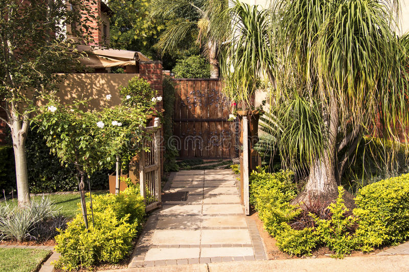 Garden Gate Entrance. Garden gate with hedge and other trees royalty free stock photos