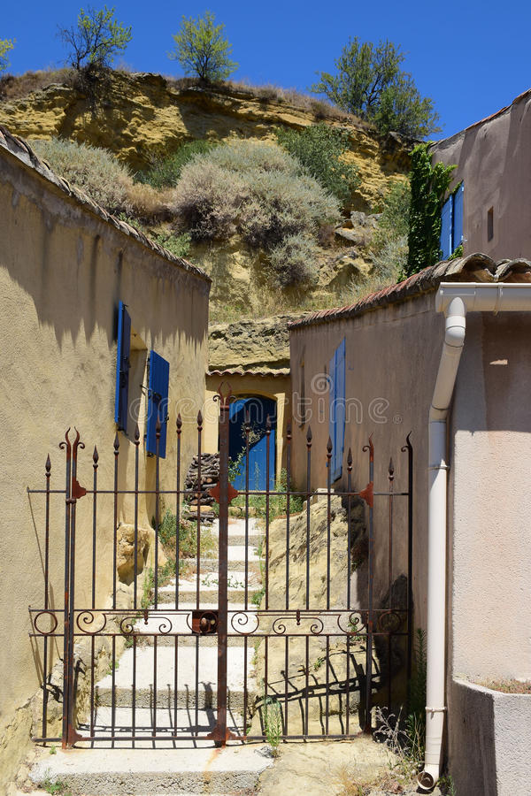 Garden gate between typical houses in a small mountain village,. Garden gate between typical houses with blue shutters in the small mountain village of Cadenet stock photo
