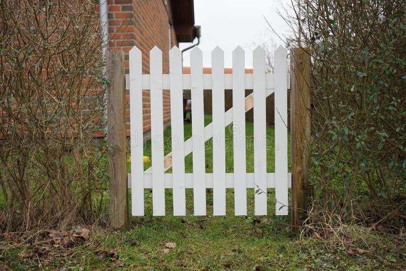 Garden gate. White garden gate and bushes stock photography