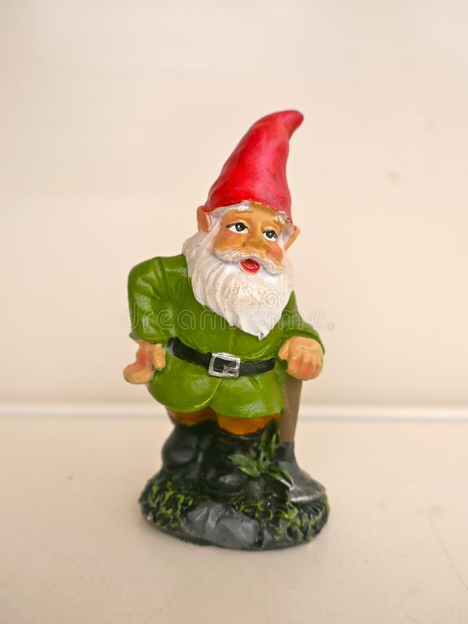 Garden gnome in front of a neutral background. Funny garden gnome in front of a neutral background royalty free stock images