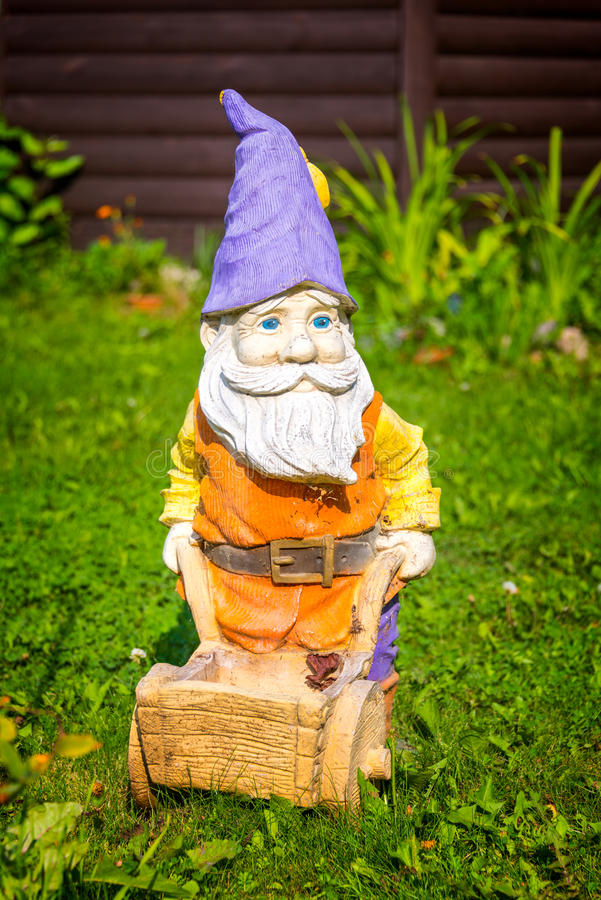 Garden gnome with a wheelbarrow in a garden. Garden gnome with a wheelbarrow in a home garden stock photo
