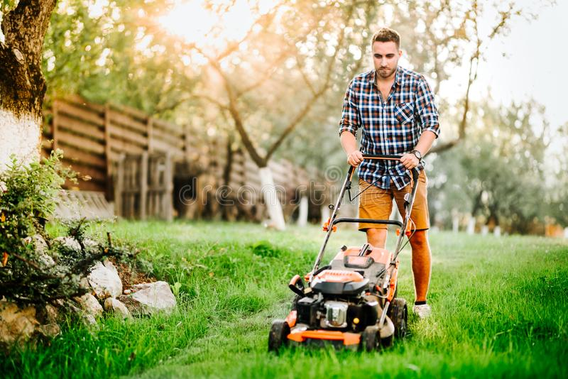 Garden and grass maintenance details - close up view of grass mower and worker stock photography
