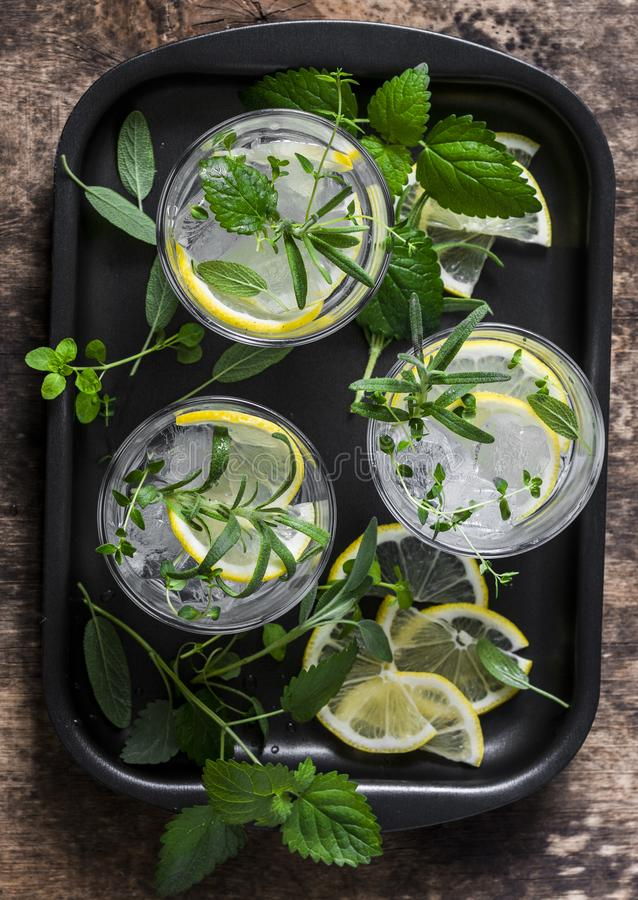 Garden herbs lemonade. Infused water with lemon, rosemary, thyme, sage and mint on wooden background, top view. royalty free stock photography